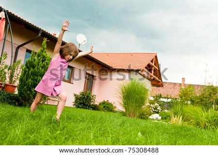 Small girl making cartwheel on garden with family house in background - stock photo