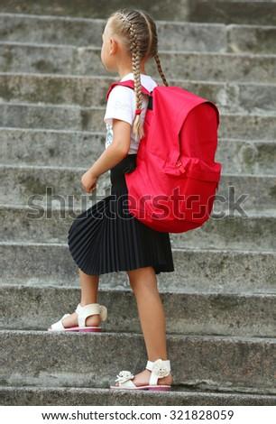 Small girl near school - stock photo