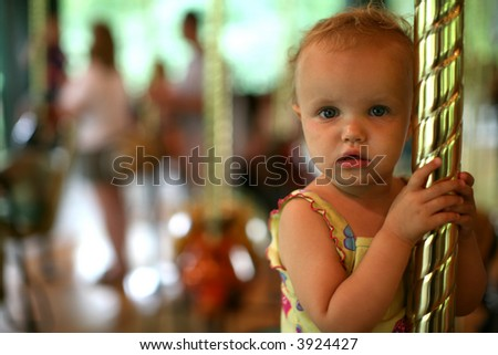 small girl on a Merry go round - stock photo