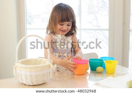 Small girl playing and painting Easter eggs in a room with a lot of sun light