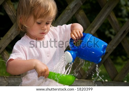 small girl playing with a watering can - stock photo