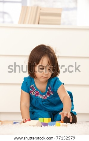 Small girl playing with building block at home, on floor, concentrating.? - stock photo
