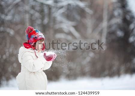 Small girl playing with snow - stock photo