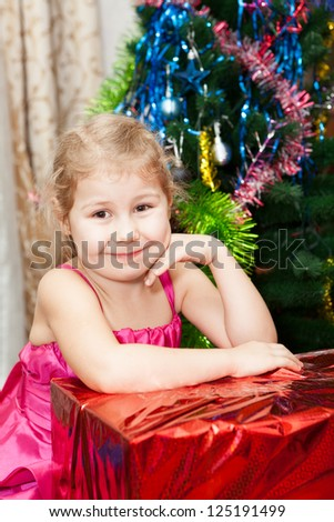 Small girl portrait with gifts near Christmas tree