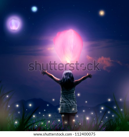 Small Girl Releases a Glowing  Sky Lantern Up on a Night Sky. Fantasy Scene and Lantern Festival Concept. Healing, Solitude and Condolences Theme. - stock photo