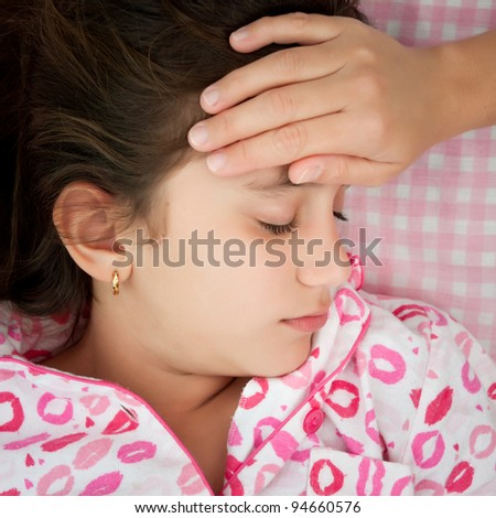 Small girl sick with fever and a woman's hand touching her forehead - stock photo