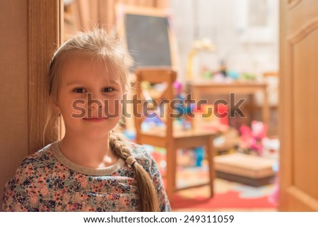 Small girl sitting in doorway in her room with games and toys - stock photo