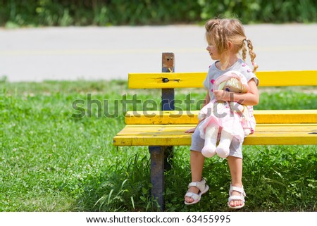 Small girl sitting on the bench in park - stock photo