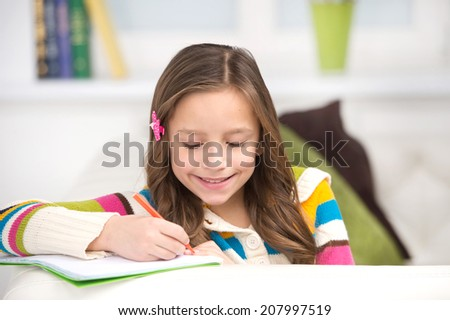 small girl sitting on white couch. cute brunette kid writing in notebook