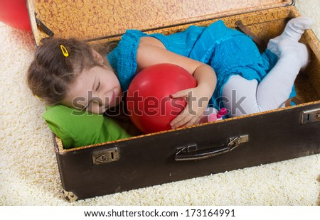 Small girl with a red ball lying in an old suitcase - stock photo