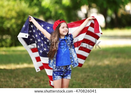 Small girl with American flag in park
