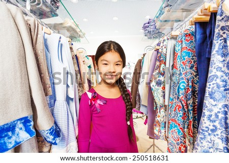 Small girl with braid between clothes hangers
