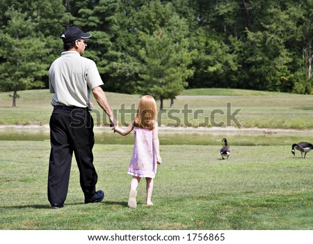 Small girl with father or grandfather walking around pond at golf course. - stock photo