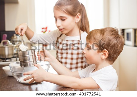 Small girl with her brother put flour into the sieve. Children cooking background - stock photo