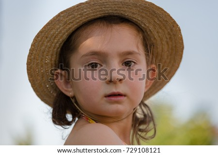 small girl with straw hat looking into the camera