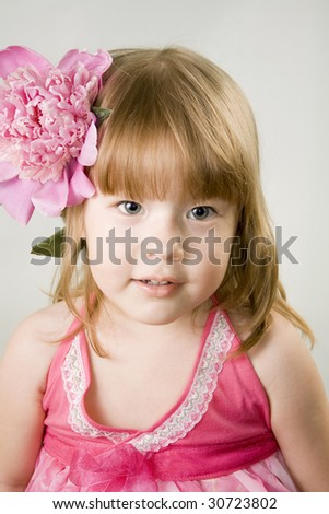 Small girl with the pink  flower in her hair - stock photo