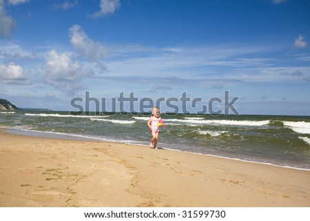 small girl with toys on the seashore
