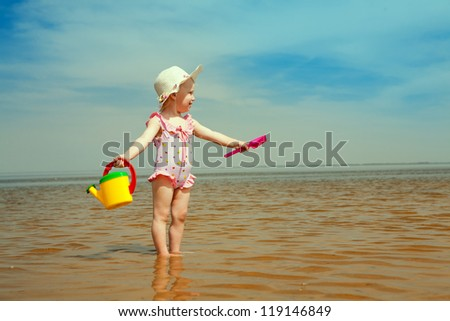 small girl with watering-pot on the seashore