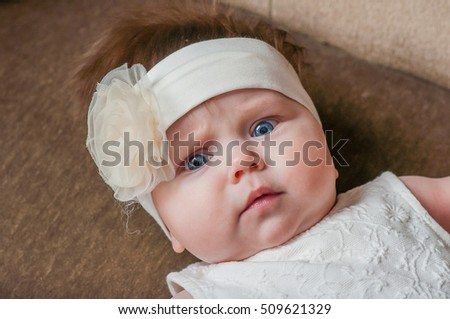Small girl with white flower on her head lie on a couch and watch
