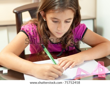 Small girl working on her school project at home - stock photo