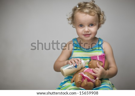 Small girls feeding her  baby  - toy