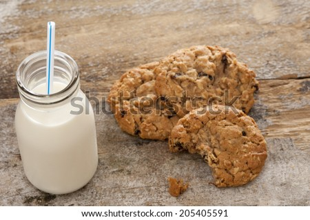 Small glass bottle of fresh creamy farm milk with a straw alongside half eaten crunchy cookies on a rustic wooden surface, high angle view - stock photo