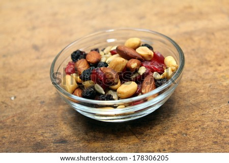 Small glass dish of trail mix on counter top - stock photo