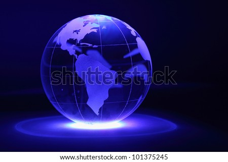 Small glass globe is illuminated by blue light from below in dark; North and South America - stock photo