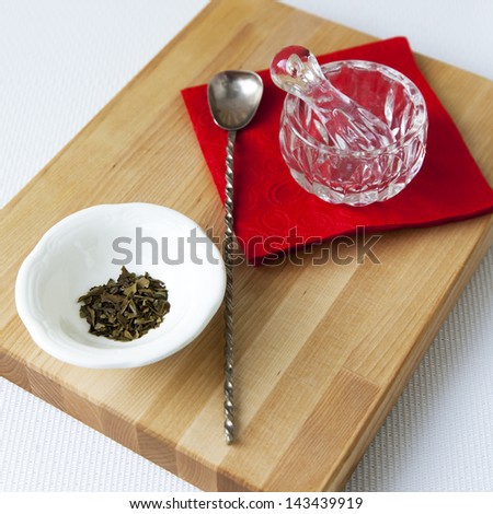 Small glass mortar with a pestle on a red napkin and spice