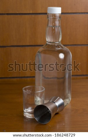 Small glass of Vodka on a wooden table with a bottle and measuring cup - stock photo