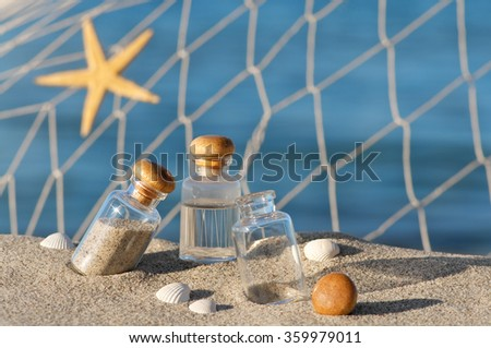 Small glasses with sand and seawater, sea star, shells and fishing net arranged on sandy beach; Vacation souvenirs - stock photo