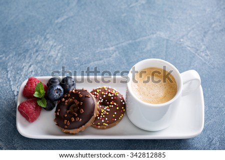 Small glazed mini donuts and coffee in an espresso cup - stock photo