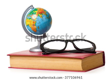 Small globe and eyeglasses on book, isolated over white background - stock photo