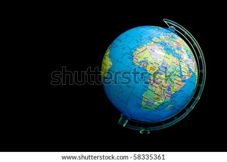 Small globe on black background - stock photo