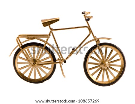 Small gold color toy bicycle figure isolated on white background. - stock photo