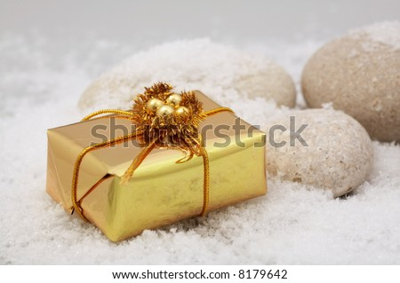small golden gift box and stones in the snow - stock photo