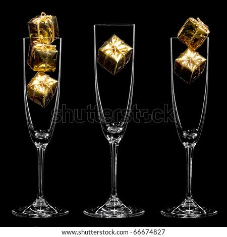Small golden gift boxes inside champagne glasses on the black background - stock photo