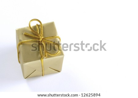 small golden wrapped present tied with gold string isolated over a white background