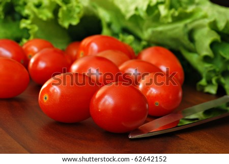Small grape tomatoes and leaf lettuce on wooden cutting board with knife.  Macro with shallow dof. - stock photo
