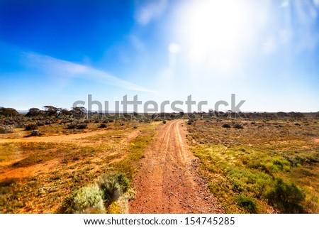Small gravel road in Australian outback in bright sunshine - stock photo
