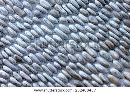 Small gray pebbles stone wall for background. - stock photo
