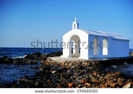 Small greek church standing on sea shore, Crete, Greece - stock photo
