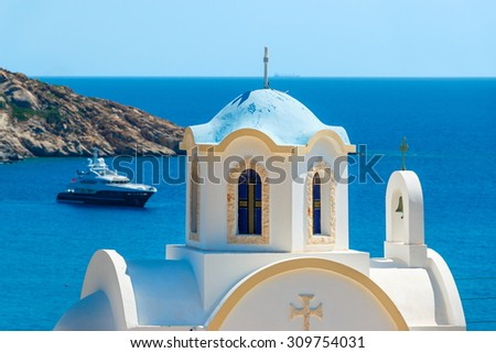 Small Greek church with blue dome against the sea - stock photo