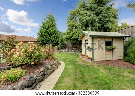 Small green fenced back yard with garden and shed. - stock photo