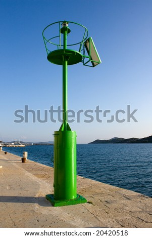 Small green lighthouse on harbor entrance