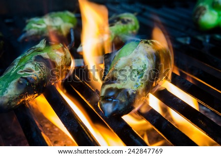 Small green peppers roast on flames on a grill - stock photo