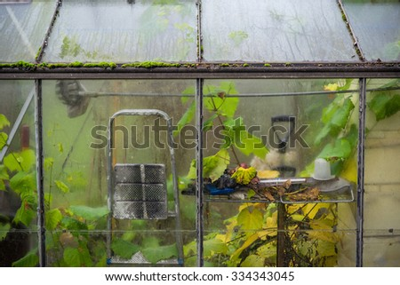 Small greenhouse with tools in the autumn