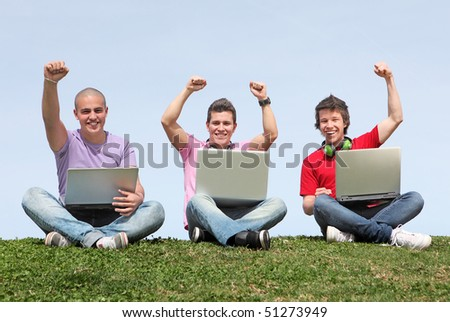 small group of boys or men with laptops and cheering happy. - stock photo