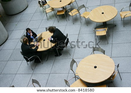 small group of business people conversing at table - stock photo
