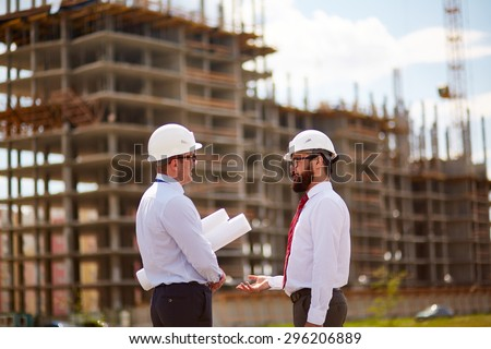 Small group of businessmen in helmets and formalwear talking in front of unfinished construction - stock photo